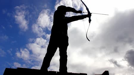 okçuluk : Silhouette of man using bow and arrow Stok Video