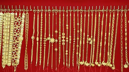 цепь : panning shot of Gold necklaces in store