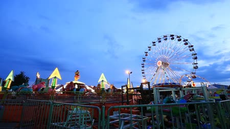 targi : Amusement park at twilight time with ferris wheel in motion
