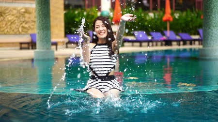 slow motion of young beautiful woman splashing water in swimming pool Wideo