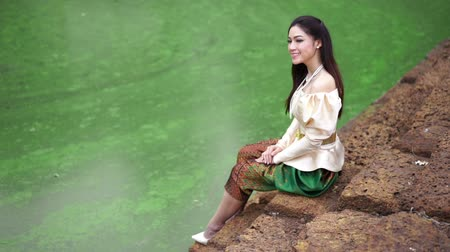 типичный : slow motion of happy beautiful woman in Thai traditional dress near the pond Стоковые видеозаписи