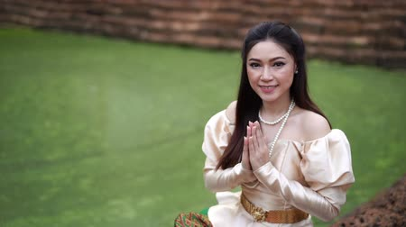 slow motion of woman in Thai traditional dress is pay respect near the pond