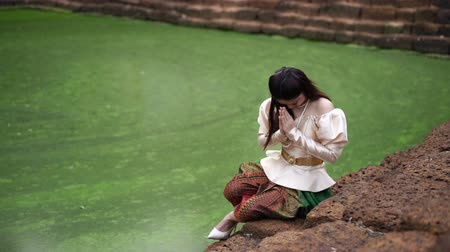 saygı : slow motion of woman in Thai traditional dress is pay respect near the pond