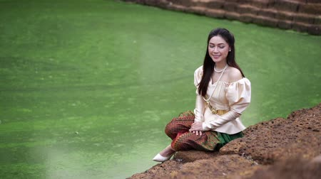 thai kültür : slow motion of happy beautiful woman in Thai traditional dress near the pond Stok Video