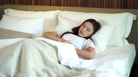 hangover : slow motion of woman with stomach ache on bed