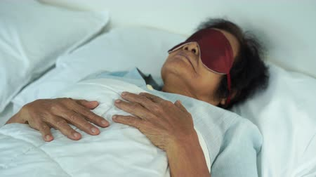 napping : senior woman with eye mask sleeping on a bed in bedroom Stock Footage