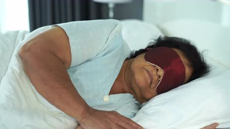 bettzeug : senior woman with eye mask sleeping on a bed in bedroom Videos