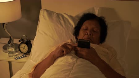 night life : senior woman using mobile phone on a bed at night