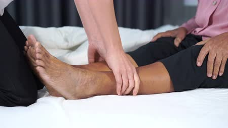guarigione : close up hands doing massage on old woman pain legs in a bed Filmati Stock