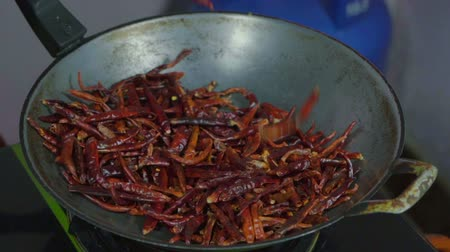 肌寒い : dried red chilies falling in a pan 動画素材