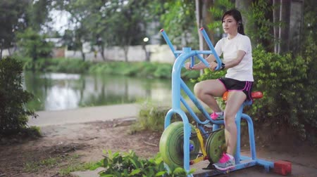 felnőtt : slow-motion of woman working out on the exercise bike in park Stock mozgókép