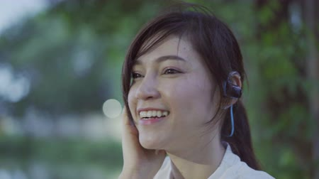 wearing earphones : sporty woman listening to music with wireless headphones Stock Footage
