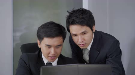 vacature : two businessman using laptop and discussing project Stockvideo
