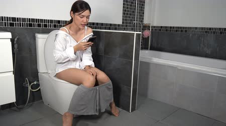 toilet paper : woman using mobile phone and sitting on toilet in bathroom