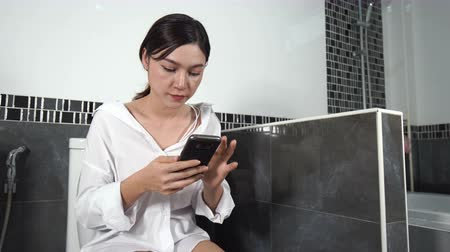 stipsi : woman using mobile phone and sitting on toilet in bathroom