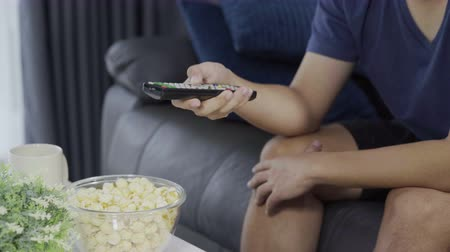 pop corn : mano con telecomando tv Filmati Stock