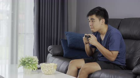 konsola : young man playing video game with joystick in the living room Wideo