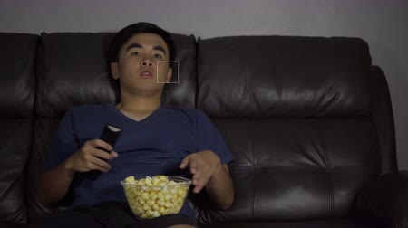choque : Shocked young man watching at tv and sitting on sofa in the living room at night Stock Footage