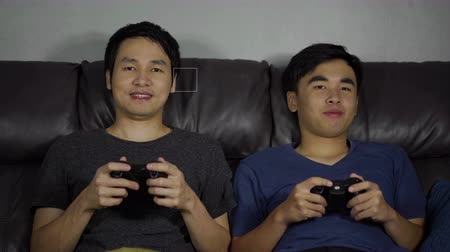 gry komputerowe : two happy man playing video games at night
