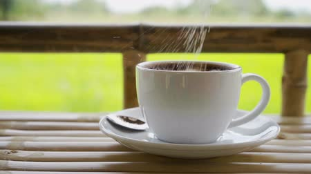 sweetener : slow-motion of strewing sugar to cup of coffee in countryside Stock Footage
