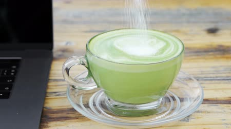 glicose : slow-motion of hand stir a cup of milk green tea