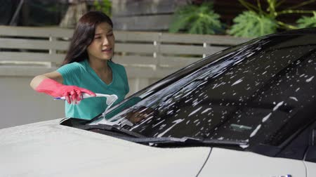 utírat : woman using squeegee to washing windshield of a car