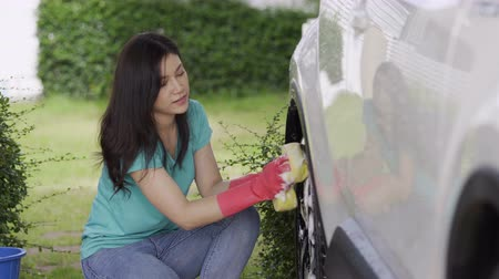 sabão : woman holding sponge washing the wheels of her car Stock Footage