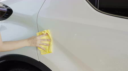 detailing : woman with microfiber cloth cleaning  a car roof Stock Footage