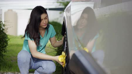 wiper : woman with microfiber cloth cleaning  a car wheel