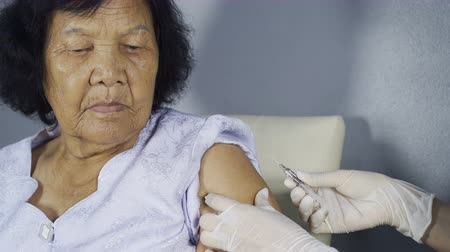 cukorbaj : Doctor giving vaccine injection into senior woman shoulder