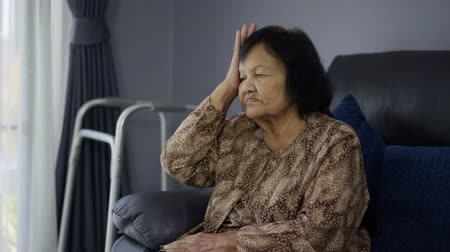 折り畳む : senior woman having a headache in living room