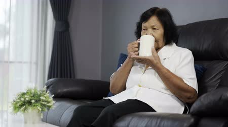 hidrasyon : senior woman drinking a cup of water in living room Stok Video
