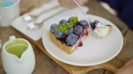 blueberry cheesecake : womans hand going to eat blueberry cheese cake