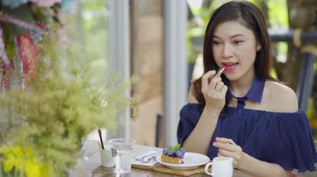 bolo de queijo : woman doing make-up with lipstick in a caf