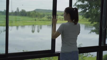 okno : slow-motion of slow-motion of woman open window and looking to nature view