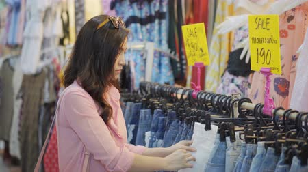 jeans short : woman choosing and buying shorts in shopping store