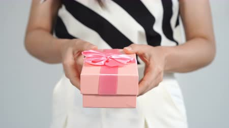 rocznica : woman holding a pink gift box in a gesture of giving.
