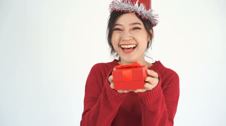 ano novo chinês : slow-motion of happy young woman with hat and holding a red christmas gift box in a gesture of giving