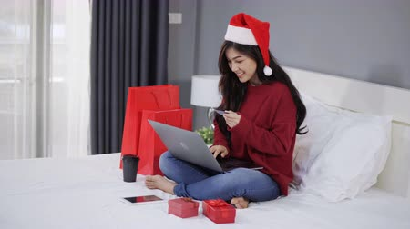 pátek : happy woman shopping online for Christmas gift with computer laptop and credit card on a bed