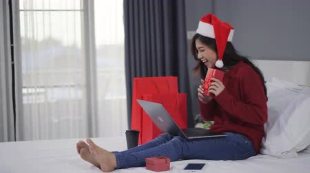 queda : happy woman using laptop computer and holding Christmas gift on a bed