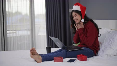 queda : happy woman using laptop computer with Christmas gift on a bed Vídeos