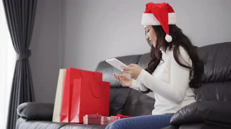 ano novo chinês : woman in santa hat shopping online for Christmas gift with digital tablet in the living room Vídeos