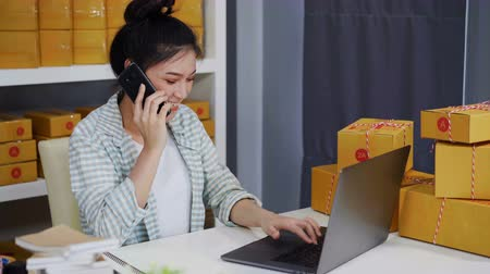 sme : young woman talking on smartphone and use computer laptop to selling product online from home office