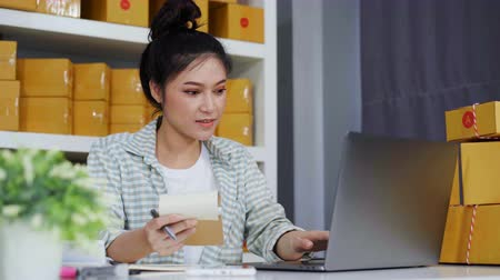 sme : happy woman working with her laptop computer and courier parcel box at home office
