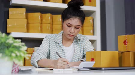 small pen : young woman entrepreneur calculating financial at home office, online market packing box delivery, startup small business owner Stock Footage