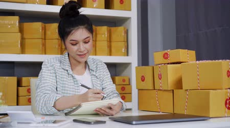 inventario : young woman entrepreneur counting parcel boxes in her own job shopping online business at home