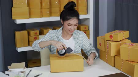 sme : young woman online entrepreneur using tape to packing parcel box at home office, prepare product for deliver to customer. Stock Footage