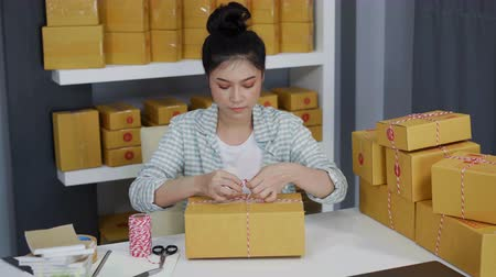 sme : young woman entrepreneur are tying ropes and packing products in parcel box, prepare for delivery to customers in home office