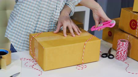 postpakketje : young woman using cutter knife open delivery parcel