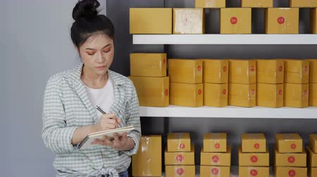チェックボックス : young woman entrepreneur counting parcel boxes in her own job shopping online business at home